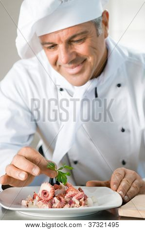 Happy smiling chef garnish a octopus salad with a leaf of persil at restaurant