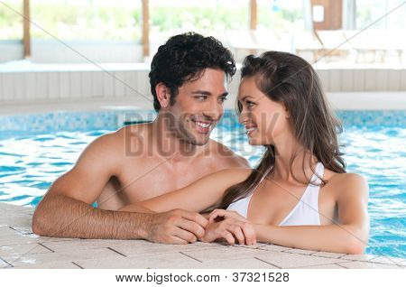 Happy smiling couple relaxing together in a pool at health spa club