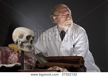 Evil Doctor With Surgical Tools And Bloody Corpse