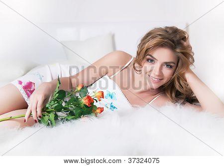 Sensual mujer acostada en una cama blanca con flores rosas