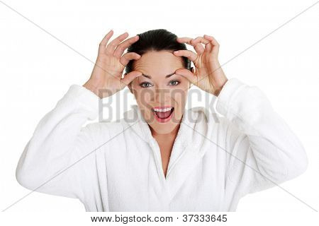 Beautiful caucasian woman checking wrinkles on her forehead, isolated on white background