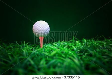 golf ball on red tee and green grass field