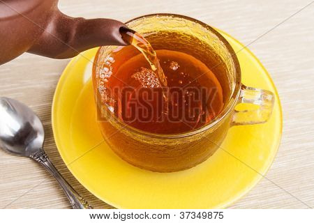Tea Being Poured Into Tea Cup With Saucer