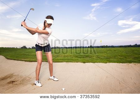 Girl golfer preparing for chipping the ball out of the sand trap.