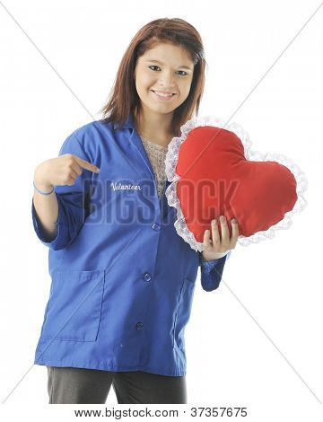 A happy teen volunteer holding a heart-shaped pillow while pointing to the word
