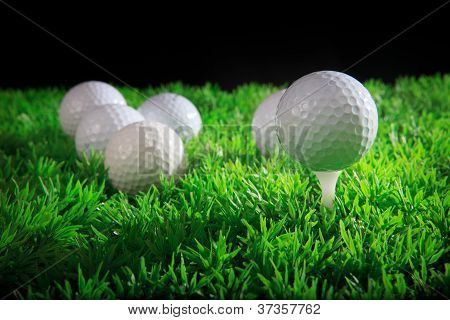 golf ball on white tee with green grass field