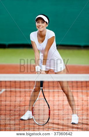 Sportswoman at the tennis court with racquet. Training