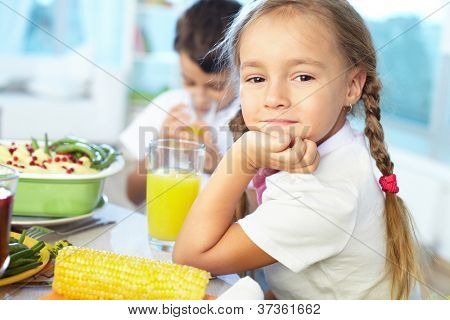 Portrait of happy girl sitting at festive table and looking at camera