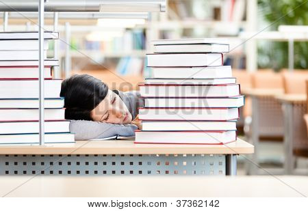 Female student sleeping at the desk with piles of books. Tired of education