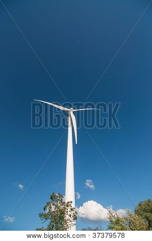 Large Wind Turbine With Trees And Blue Sky