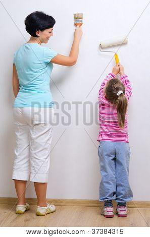 Young smiling woman and little girl with painting tools