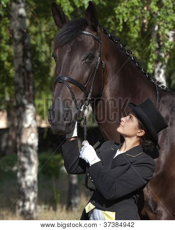 Portrait Of A Beautiful Horsewoman In Uniform Standing With Horse Outdoors