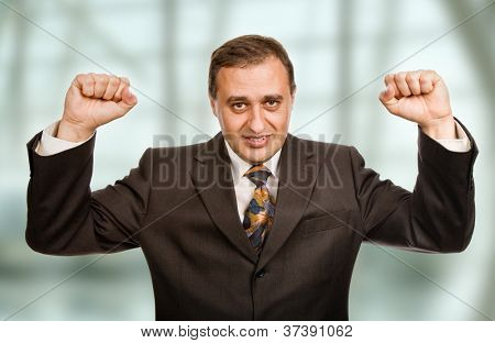 successful business man winning with arms wide open at the office