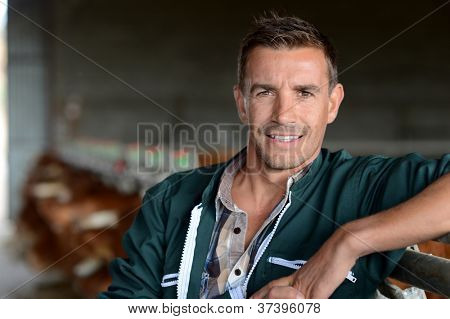 Portrait of smiling herdsman standing in barn