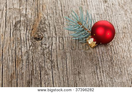 Red Christmas ball on wooden background with fir branch