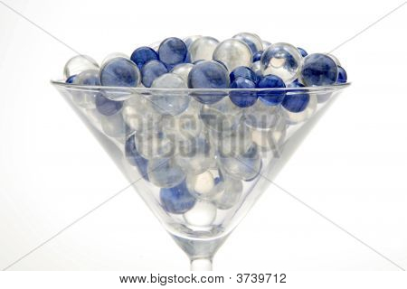 Blue And Clear Marbles Resting In A Martini Glass.
