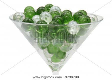 Green And Clear Marbles Resting In A Martini Glass.