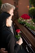 stock photo of casket  - Morning man and woman on funeral with red rose standing at casket or coffin - JPG