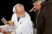 stock photo of jekyll  - Grave robber and evil doctor with bloody cleaver exchange glances - JPG