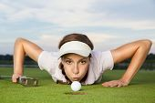 Desperate young woman golf player with putter in hand lying on green and blowing golf ball into cup,