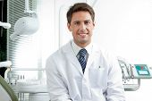 stock photo of oral  - Portrait of happy male dentist wearing lab coat while sitting in clinic - JPG