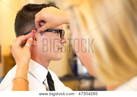 Optician Examining Correct Fit Of Eyeglass Frame For Customer