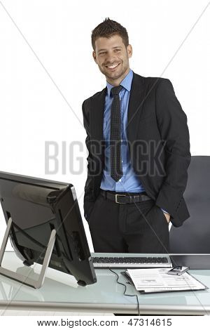 Confident young businessman standing by desk with hands in pockets, smiling.