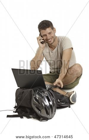 Young man sitting in tailor seat, using laptop computer, talking on mobilephone, having helmet and backpack, smiling.
