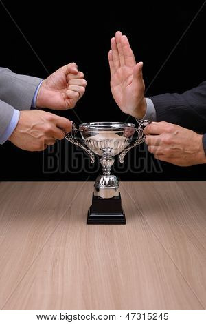 Business rivalry and confrontation at work, two businessmen fighting over a silver trophy