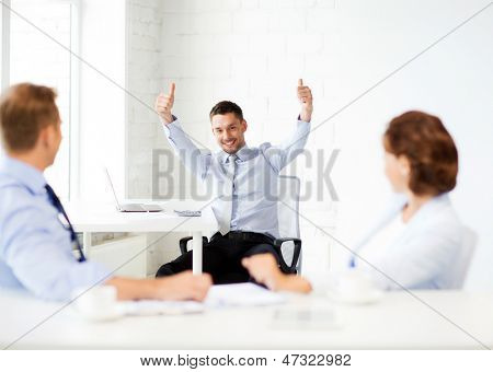 picture of happy businessman showing thumbs up in office