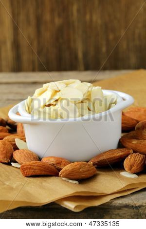 whole nuts and blanched almonds in white bowl