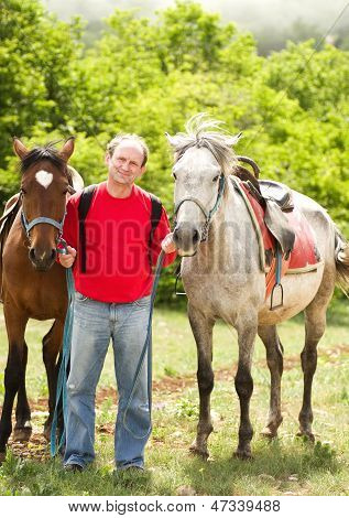 Handsome smiling man with horses in the forest