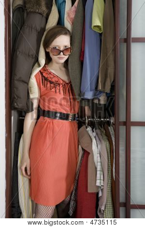 Girl Wearing Stylish Glasses Go Out From Wardrobe. Young Attractive Woman Check Clothes Before Shopp