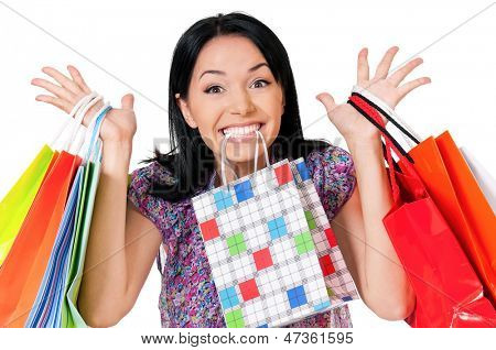 Shopaholic shopping woman holding many shopping bags, isolated over white background