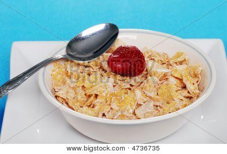 Taça de flocos de cereais com morango e colher