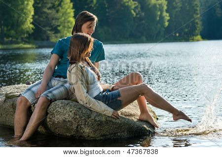 Couple sharing a romantic moment sitting on rock sunset