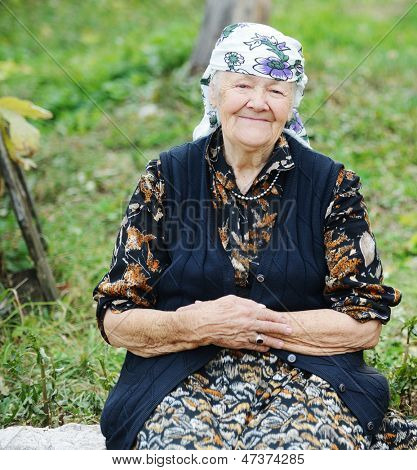 Very aged woman sitting in nature, portrait