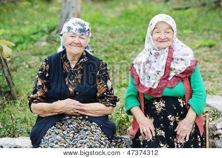 Two elderly women sitting outdoors
