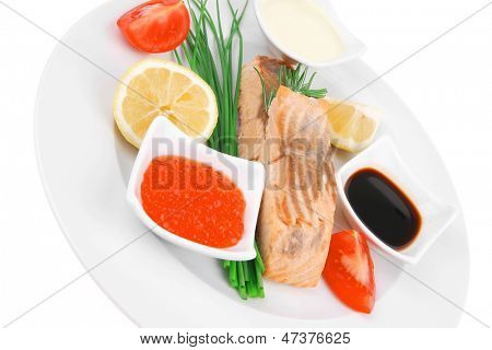 savory sea fish entree : roasted salmon strips with green onion, red caviar , mayonnaise and soybean sauces , and tomatoes on white dish isolated over white background