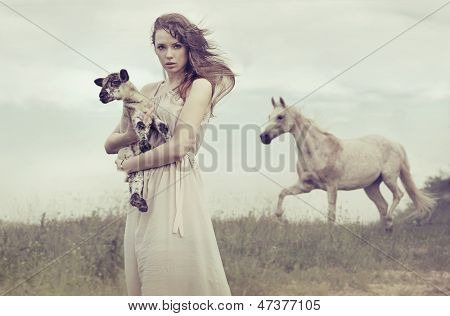 Young woman holding a small lamb