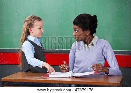 Young African American female teacher smiling while looking at schoolgirl in classroom