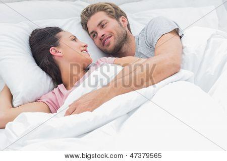 Paar umarmen und Blick auf einander, während sie im Bett liegen