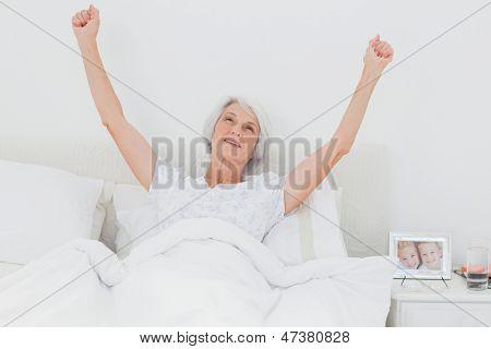 Mujer madura despertando y levantando los brazos en la cama