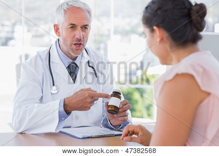 Doctor explaining the pills to patient in the office at desk