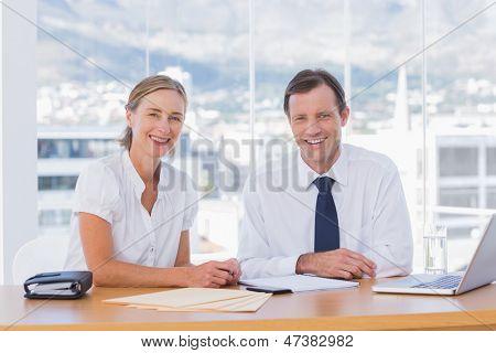 Lächelnd Geschäftsleute posieren zusammen, während sie arbeiten