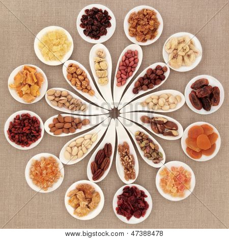 Large dried fruit and nut selection in white porcelain bowls over hessian background.