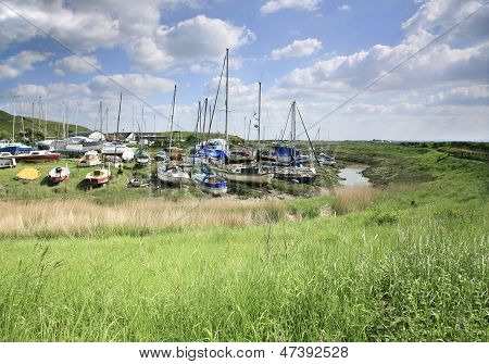 Boats moored on the banks of the river Axe near Weston Super Mare, Somerset