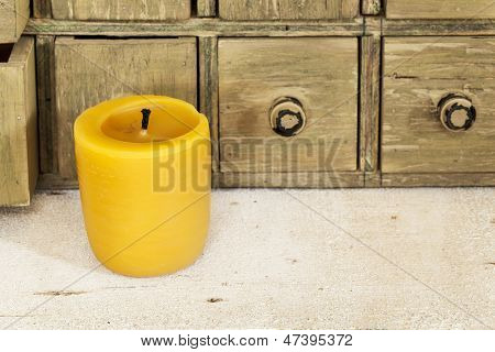 bee wax candle in retro setting with a primitive apothecary drawer cabinet