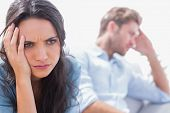 picture of frown  - Irritated woman holding her head in the living room - JPG