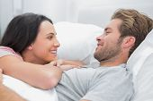 image of quilt  - Cheerful couple awaking and looking at each other in bed - JPG